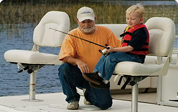 Dad helps his boy fish from a pontoon boat